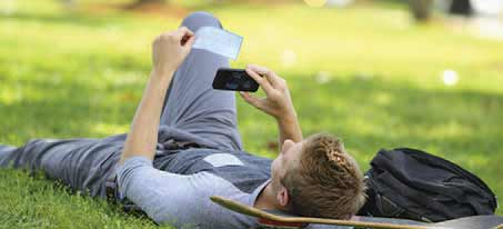 man laying in the grass with a skateboard as he takes a photo of a check with his mobile device